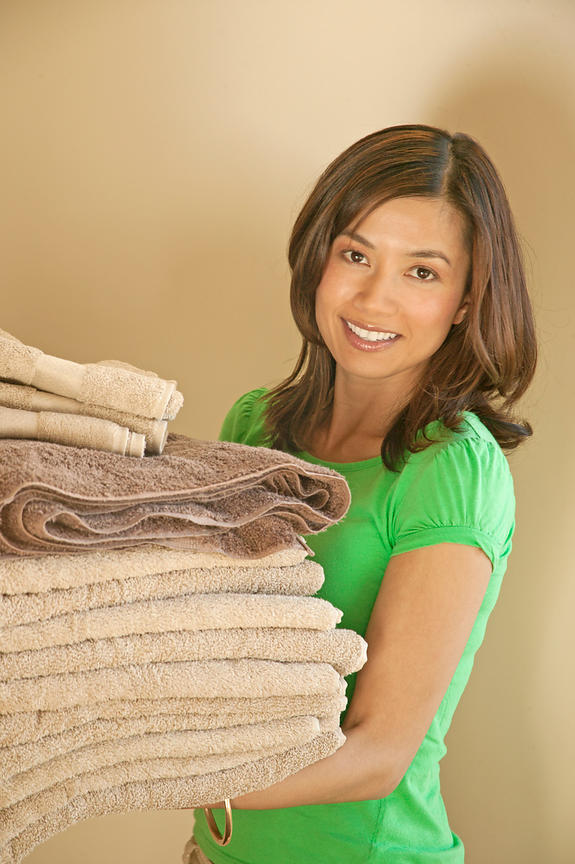 woman holds stack of clean towels