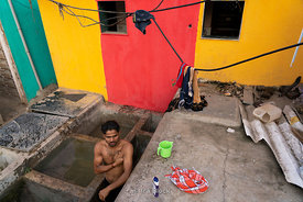 A man bathing at Dhobi Ghat, a laundry district in Mumbai, India.