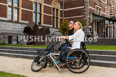 Couple using power wheelchairs in an historic courtyard