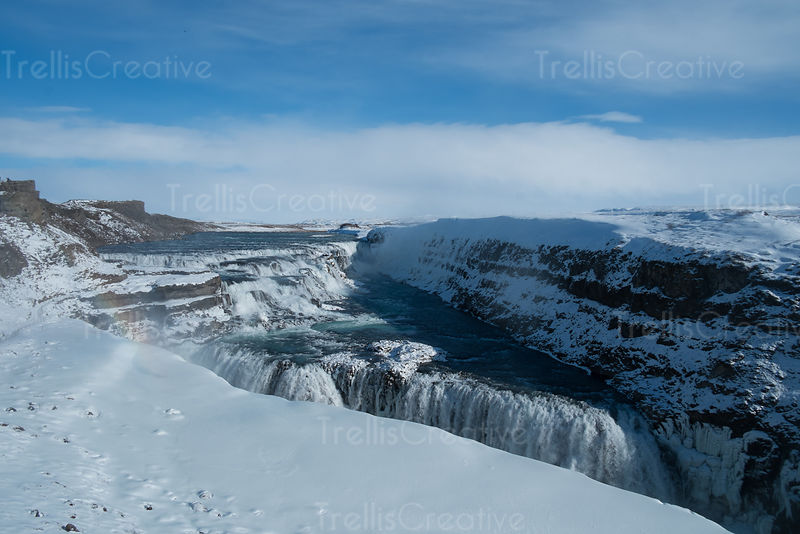 A small rainbow appears over Gulfoss waterfall in Iceland
