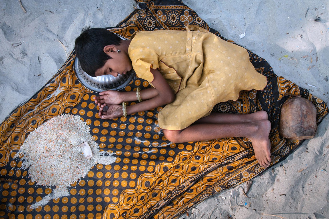 A girl falls asleep clutching a coin while panhandling for money or rice (left) at the Gangasagar Mela, a Hindu pilgrimage to Sagar Island in the Bay of Bengal in India, where the Ganges meets the sea. Not staged. Taken with permission of her parents.