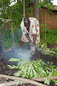 Woman preparing a fire pit to make charcoal to sell at market. Kenya.