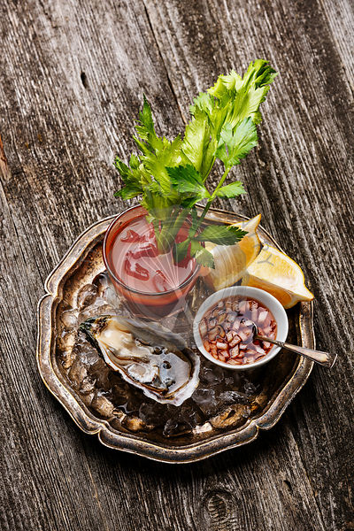 Shucked Oyster Fines de Claire and Bloody Mary cocktail on gray wooden background