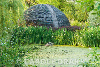 Dome structure made of thousands of bottles seen beyond lake and Iris pseudacorus var. bastardii. Westonbury Mill Water Garden, Pembridge, Herefordshire, UK