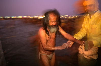 India - Allahbad - A man is helped from the water after a dip in the Ganges, Ardh Kumbh Mela 1995, Allahbad, India