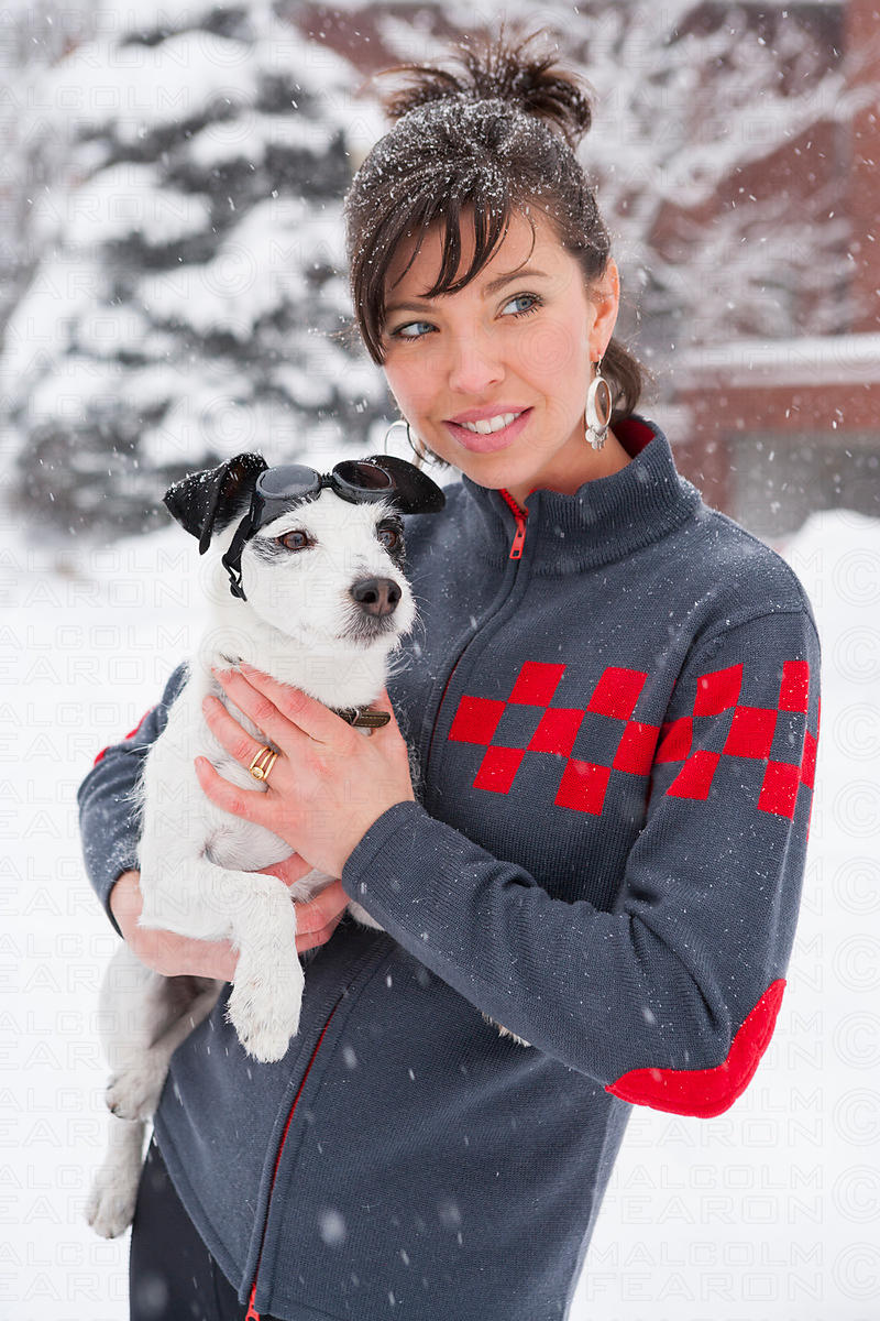 neve sweater girl holding dog with sunglasses in snow