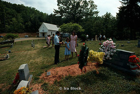 A family mourns at a cemetary.