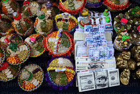 Miniature pots of seeds and beans and money bundles in market for Alasitas festival, Puno, Peru