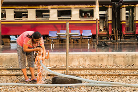 A mother washes her child at the Bangkok Rail Station in the Pathum Wan District in Thailland. Also known as Hua Lamphong Station.