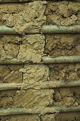 Detail of mud hut wall showing baked mud and wooden supports Kenya Africa
