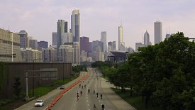 "Medium Shot: Sunrise As ""Bike The Drive"" Riders Emerge From Chicago Skyline"
