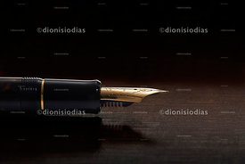 Golden feather of fountain pen in macro over dark wood background