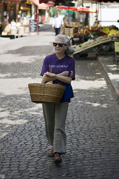 France - Paris - A woman with her shopping basket walks through the market on the Rue Mouffetard.