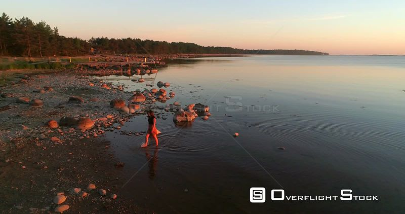 Woman walking up from the water, aerial view around a on a girl enjoying a warm sunset, on a sunny summer evening dusk, Hanko, Uusimaa, Finland