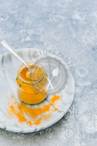 Turmeric in a jar with spoon on a light background