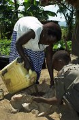 Women pouring cattle manure through cloth, to make fertiliser,  while young boy helps Uganda Africa