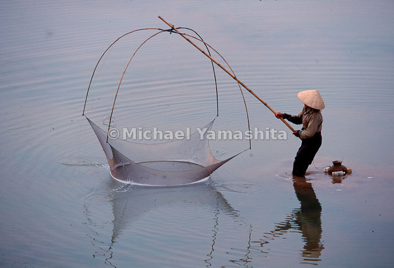 A woman practices the ancient art of dip-net fishing in the shallow water along the banks on Vientiane, Laos' sleepy capital city.
