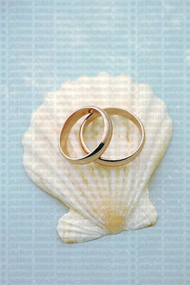 Rose gold wedding rings with seashell on blue wood background Wedding invite with copy space