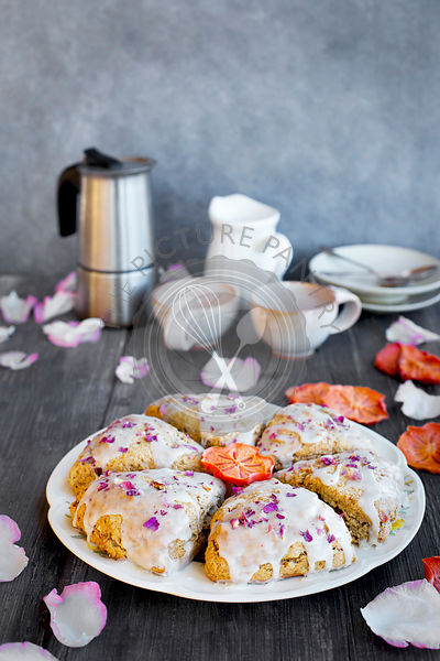 Persimmon Rose Scones served with espresso. Photographed from front view on a rustic gray wood background.