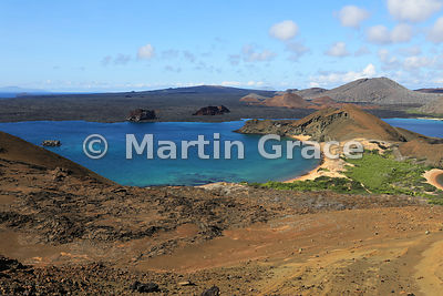 Classic view from the summit viewpoint of Bartolome Island across Bartolome's south-facing beach to the lava flows, cinder cones and tuff cones of Santiago, Galapagos Islands