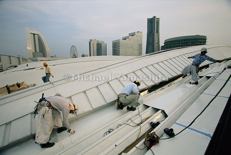 Workers teeter and toil on a giant gamble: the Yokohama convention center. While vacancy rates are high in some areas, falling land prices and government subsidies are fueling a construction boom. Years of lavish government spending on public works have saddled Japan with the industrialized world's biggest national debt.