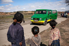 Children look at a prototype of the new Karenjy Mazana II car on road 7 near Fianarantsoa, southern Madagascar on August 5, 2014.