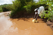 Woman getting water out of a muddy river for use  as drinking water. Kenya.