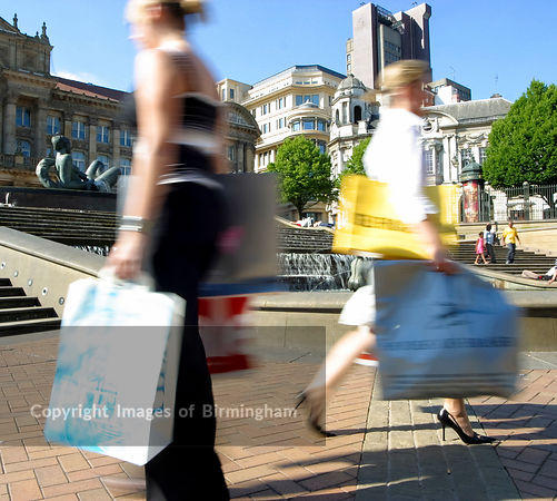 Sale season in Birmingham City Centre. Women with shopping bags in Victoria Square.  In the background is Birmingham Council House and The River artwork.