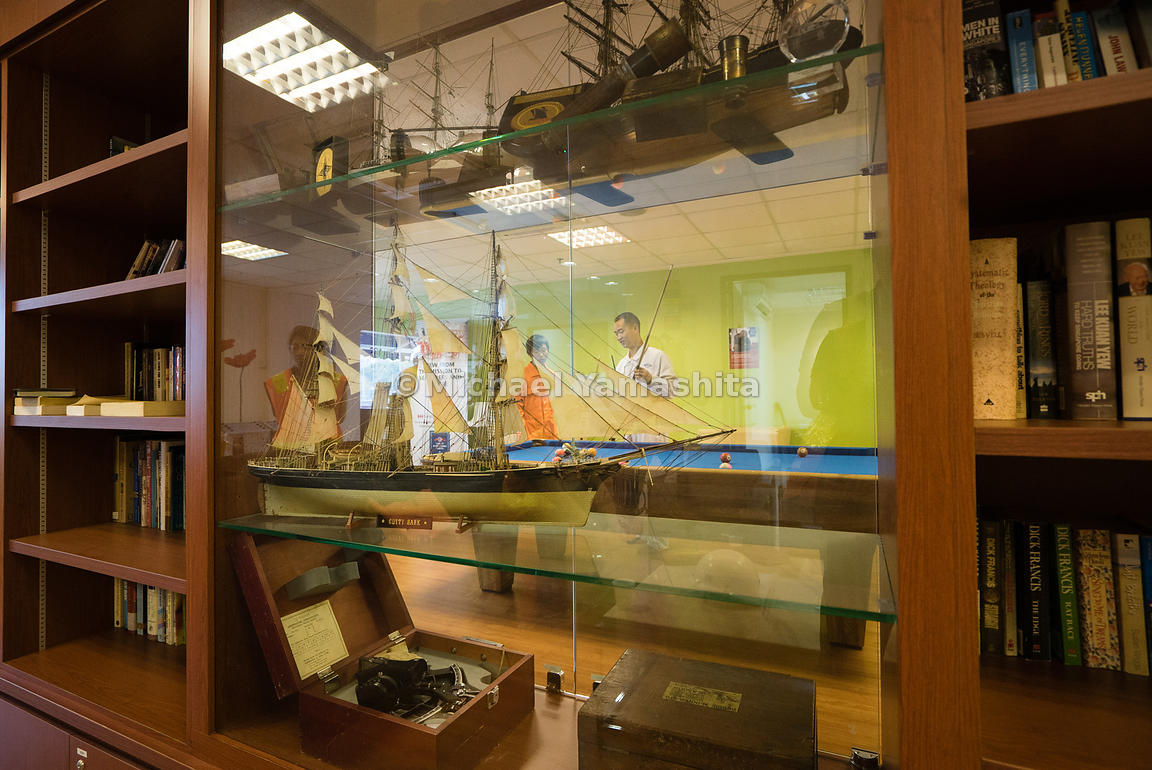 Standing proud on a glass shelf overlooking the recreation room, an ornate miniature model of a mariner's sailing ship pays homage to Singapore's maritime past.