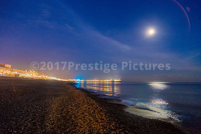 Moonlight reflecting across the sea as the Lights of Brighton shine in the distance