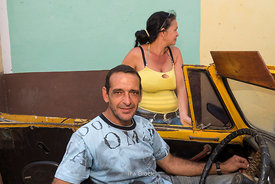 A man in a parked car and a woman standing right next to the car on the street in Trinidad, Cuba.