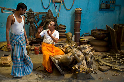 India - Swamimalai - Master craftsman Pranava Stapathy instructs another craftsman whilst working on a large statue