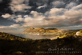 View of Simon's Town, bay and harbour from Elsie's Peak, mountain fynbos plants in foreground,cumulus clouds in sky