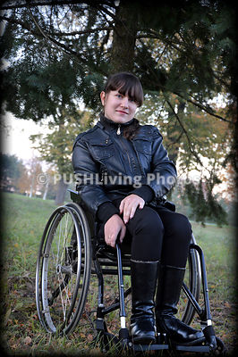Young woman in a wheelchair in a leather jacket in a park
