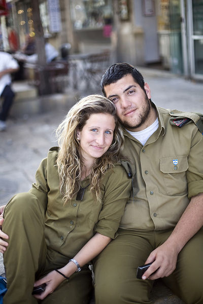Israel - Jerusalem - A young Israeli couple in uniform sit on a bench on Ben Yahuda Street