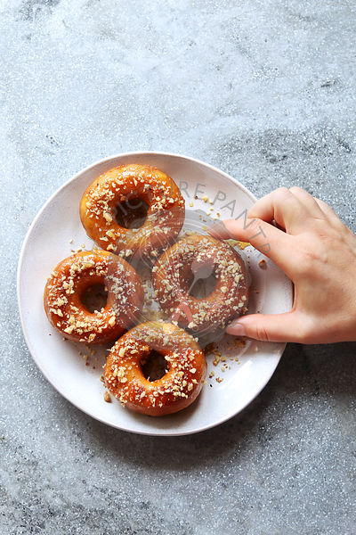 Female hand grabbing a donut with honey maple syrup and ground walnuts from a plate.Top view