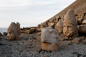The west terrace of Mount Nemrut with heads of the colossal statues and the tumulus.  Heads of Zeus-Oromasdes, Commagene, Apollon-Mithras, Heracles-Artagnes and a guardian eagle. The UNESCO World Heritage Site at Mount Nemrut where King Antiochus of Commagene is reputedly entombed.