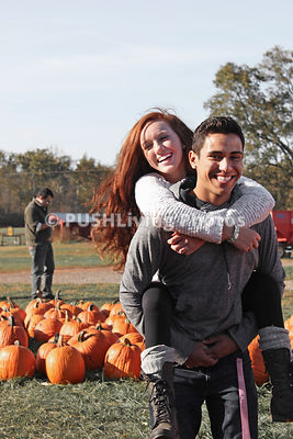 Young woman in a wheelchair gets a piggy back ride in a pumpkin patch