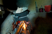 Cooking meal over an open fire in a small basic kitchen unit, Kenya.