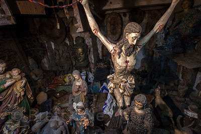 A wooden figure of Jesus on the cross, among other religious figures, in the dusty backroom of a shop at Chor Bazaar, also known as the Thieves Market, Mumbai, India.