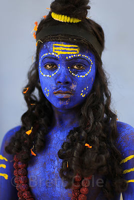 A boy dresses as Shiva in blue with a yellow tripundra to pose for photos with tourists, Pushkar, Rajasthan, India