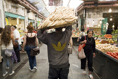 Israel - Jerusalem - A man carries bread on a try through the Mahane Yahuda Market