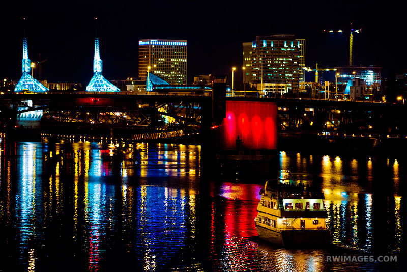 BOAT APPROACHING A CITY BRIDGE WILLAMETTE RIVER DOWNTOWN PORTLAND OREGON AT NIGHT COLOR