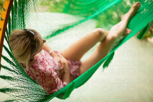 woman relaxing in green string hammock