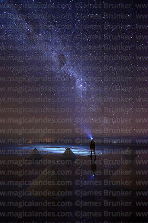 Tourist wearing headtorch standing next to salt cones looking at Milky Way in rainy season, Salar de Uyuni, Bolivia