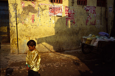 India - New Delhi - A performers son in a gold shirt