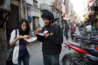 India - New Delhi - A young couple eat pizza outside a pizza shop