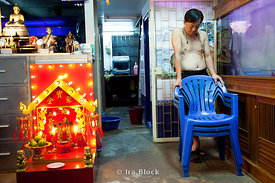 A man stands near a fish tank in his shop in Bangkok, Thailand; to his left is a shrine.