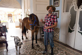 A  horse whisper with a horse and a dog at his home in Trinidad, Cuba.