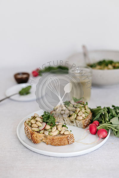 Warm white bean arugula salad served on bread.